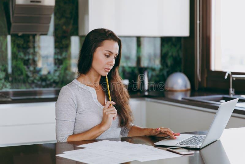 Una mujer joven pasa tiempo en casa, en la cocina y en el roo imagen de archivo