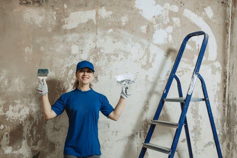 Una mujer joven preparada para hacer las reparaciones, situación sonriente del rato en el fondo de una pared pintada, imágenes de archivo libres de regalías