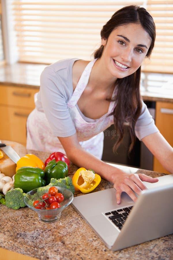 Una mujer joven que busca una receta en el Internet imagen de archivo libre de regalías
