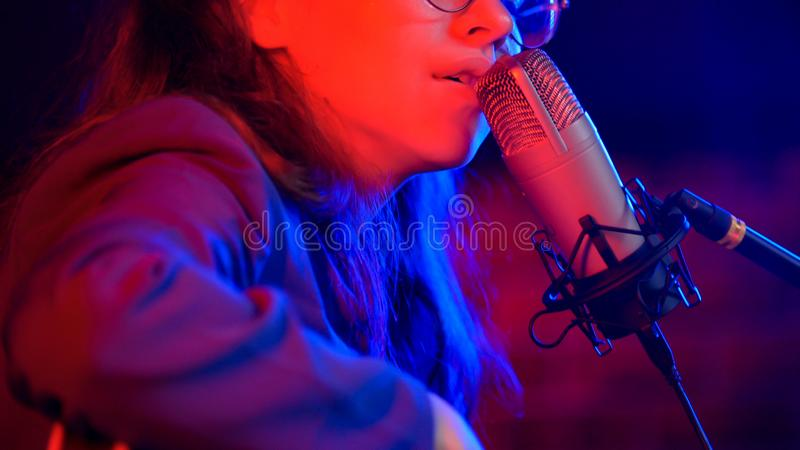 Una mujer joven que canta por el mic en la iluminación de neón en el estudio fotografía de archivo libre de regalías