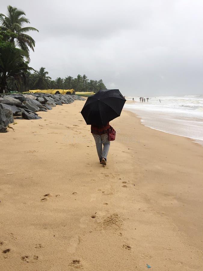Una mujer joven que da un paseo en las playas de Kundapura debajo de un paraguas fotos de archivo