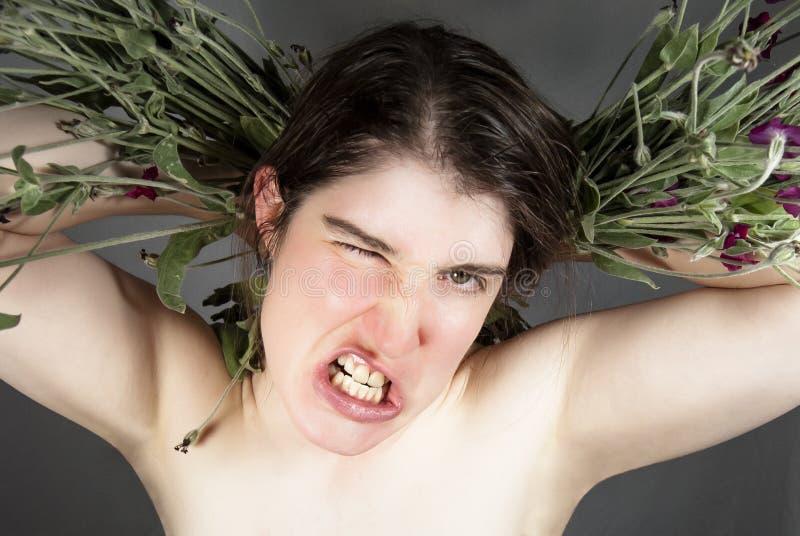 Una mujer joven que gruñe con las flores imagenes de archivo