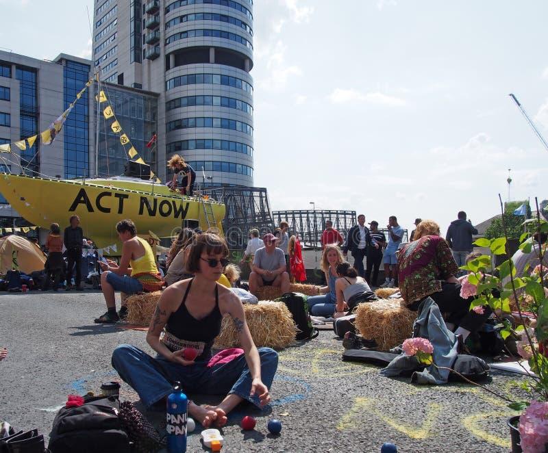 Una mujer joven que hace juegos malabares delante del barco amarillo grande en la protesta de la rebelión de la extinción que blo foto de archivo libre de regalías