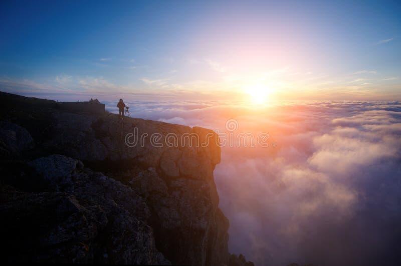 Una mujer joven que hace una película en las montañas brumosas en la puesta del sol imagenes de archivo