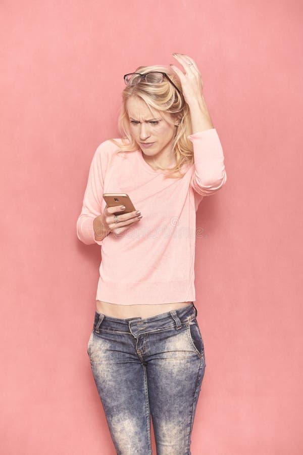 Una mujer joven que mira a su tel?fono elegante, mientras que con incredulidad usando ?l foto de archivo libre de regalías