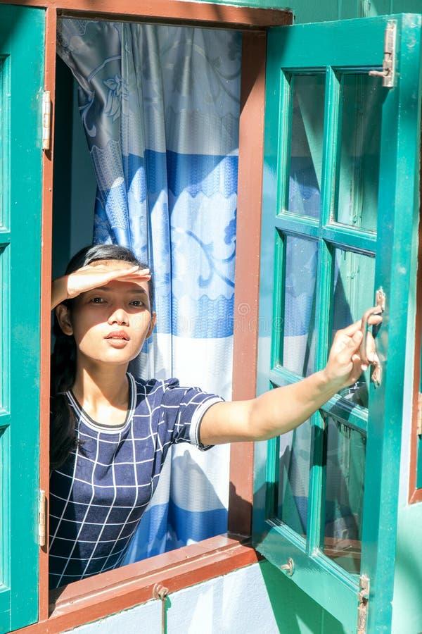 Una mujer joven que mira a través de ventana fotografía de archivo