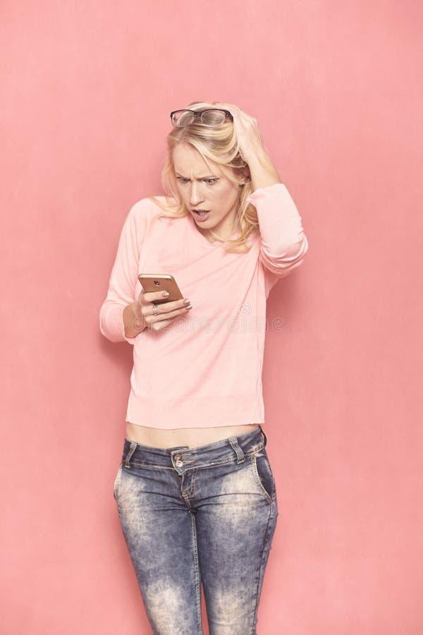 Una mujer joven que parece enojada a su tel?fono elegante, mientras que con incredulidad usando ?l imagenes de archivo