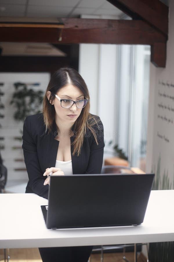 Una mujer joven que piensa, 30-39 años, tiro del cuerpo superior Trabajo en la computadora portátil en oficina imagen de archivo