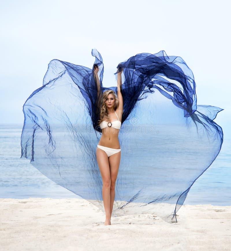 Una mujer joven que presenta con la seda azul en una playa imágenes de archivo libres de regalías