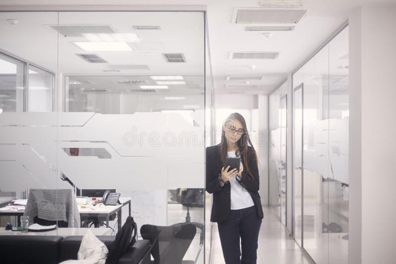 Una mujer joven que se coloca, 20-29 años, ropa casual elegante, usando la tableta en oficina interior moderna foto de archivo