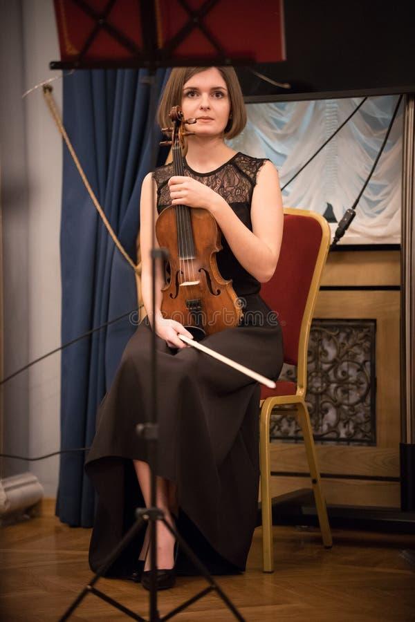 Una mujer joven que se sienta en el violín de la tenencia de la silla fotografía de archivo