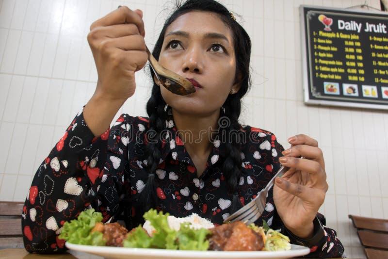 Una mujer joven que se sienta en restaurante vietnamita fotos de archivo