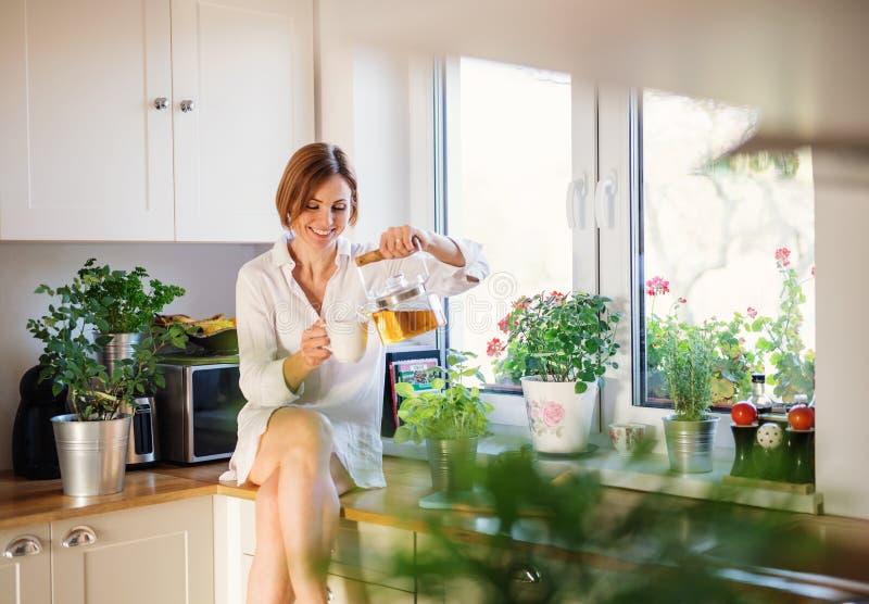 Una mujer joven que se sienta en worktop dentro en la cocina, té de colada fotografía de archivo libre de regalías