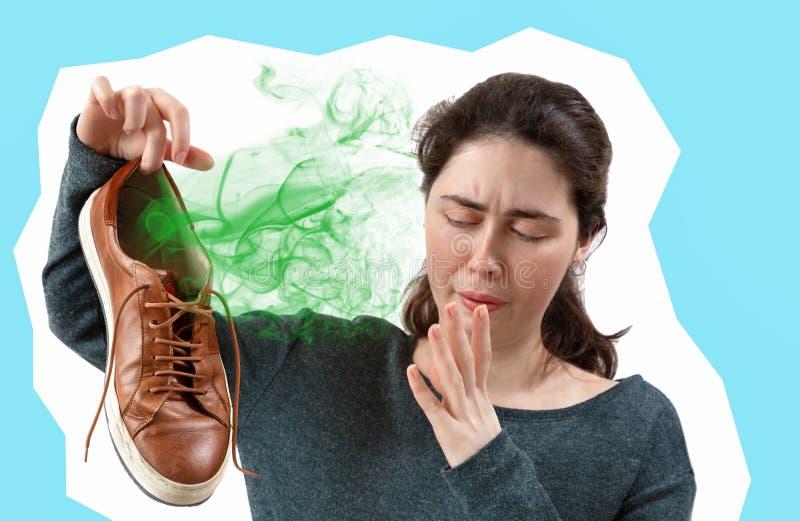 Una mujer joven que sostiene una zapatilla de deporte en su mano, que apesta fuertemente El concepto de hacer publicidad las plan imagen de archivo