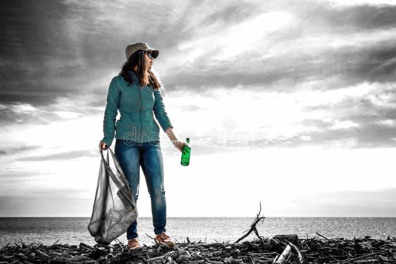 Una mujer joven se coloca con un bolso de basura y una botella en su mano Fondo blanco y negro Manteniendo el ambiente limpio tin fotos de archivo
