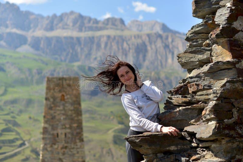 Una mujer joven se coloca sonriente cerca de una pared arruinada contra una torre fotografía de archivo libre de regalías