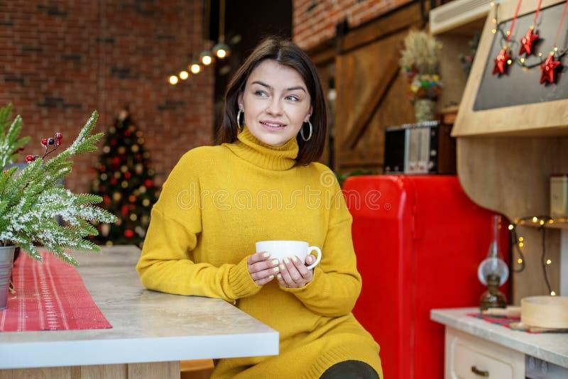 Una mujer joven se está sentando en la cocina con una taza de té en un suéter hecho punto amarillo Hogar del concepto, comodidad, foto de archivo libre de regalías