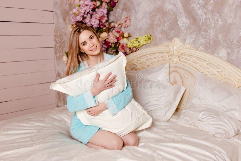 Una mujer joven se sienta en una cama y abraza una almohada fotos de archivo libres de regalías