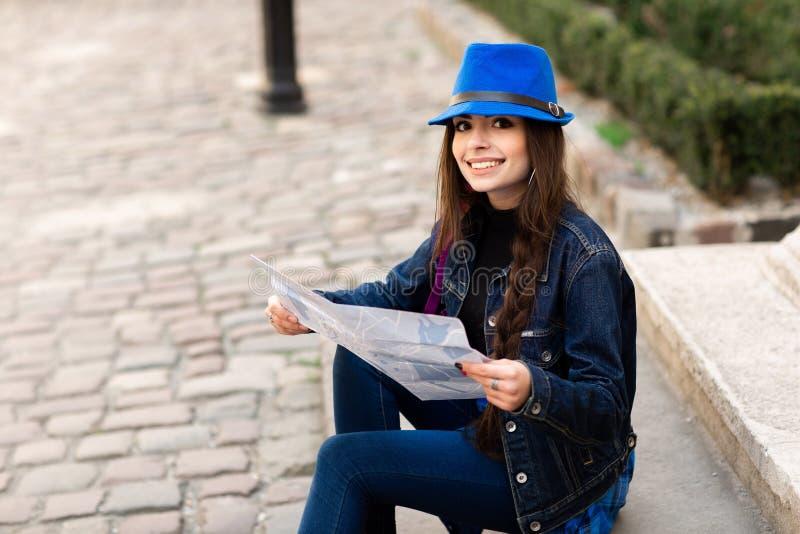 Una mujer joven se sienta en las escaleras en el patio viejo, y lee el mapa Lviv, Ucrania fotos de archivo libres de regalías