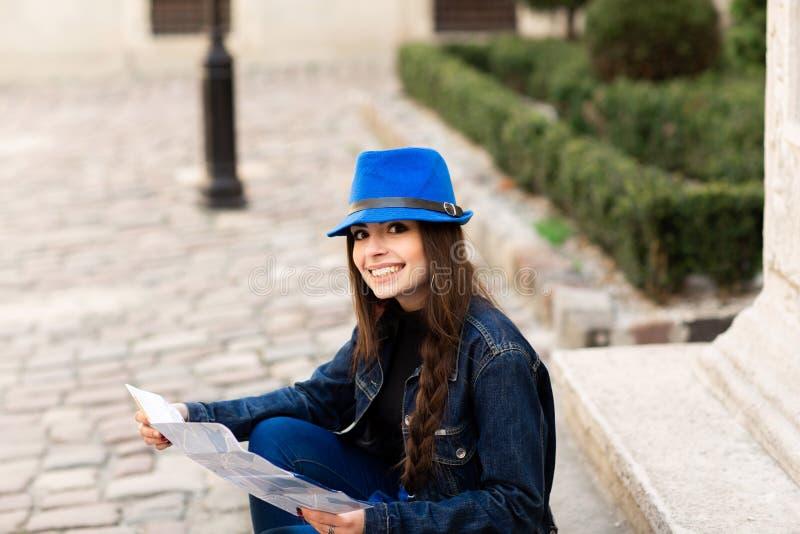 Una mujer joven se sienta en las escaleras en el patio viejo, y lee el mapa Lviv, Ucrania fotos de archivo