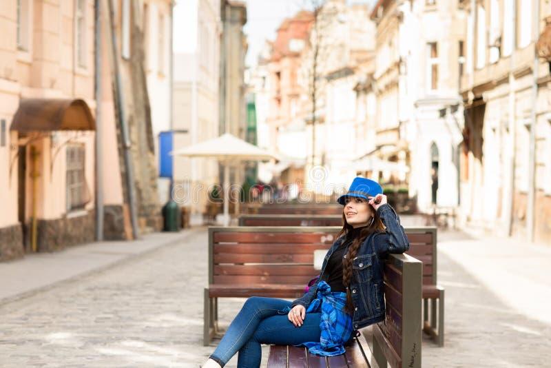 Una mujer joven se sienta en un banco en la calle vieja, y la reclinación Lviv, Ucrania fotografía de archivo libre de regalías