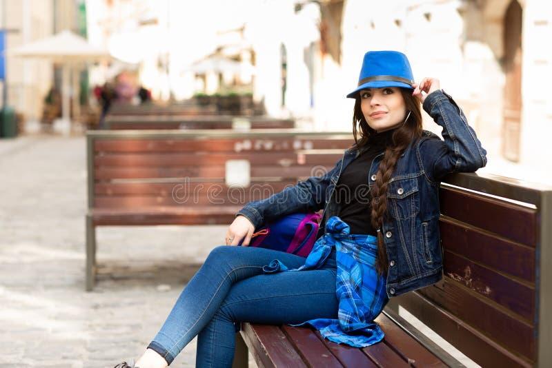 Una mujer joven se sienta en un banco en la calle vieja, y la reclinaci?n Lviv, Ucrania imagenes de archivo