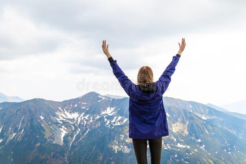 Una mujer joven siente fuerte y aumentado sus manos para arriba, disfruta de un paisaje hermoso de la montaña imágenes de archivo libres de regalías