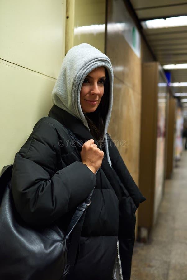 Una mujer joven sonriente que se coloca en una estación de metro fotografía de archivo libre de regalías