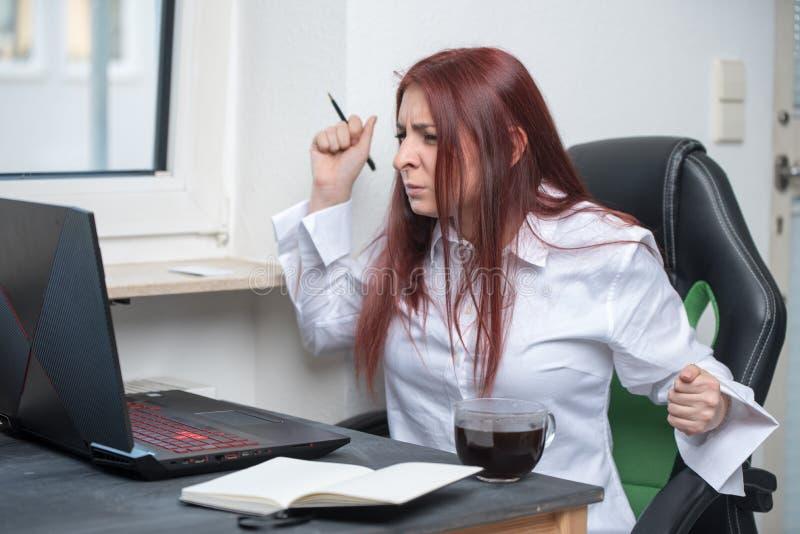 Una mujer joven subrayada, enojada se está sentando en su escritorio y está gritando en el ordenador portátil con una cólera inte fotos de archivo