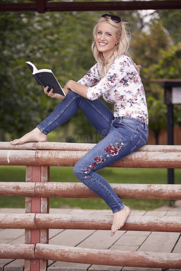 Una mujer joven, tiro integral, 25 años, inusualmente sentándose en la cerca de madera, sosteniendo un libro Sonrisa imagen de archivo libre de regalías