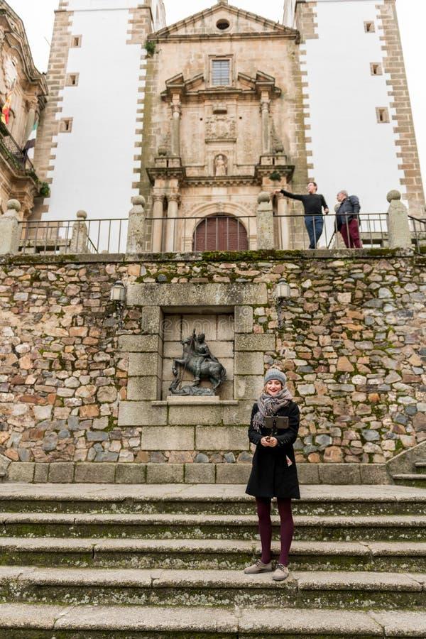 Una mujer joven toma una imagen con un palillo del selfie en la plaza de San Jorge, ciudad vieja en el fondo, Caceres, España imágenes de archivo libres de regalías