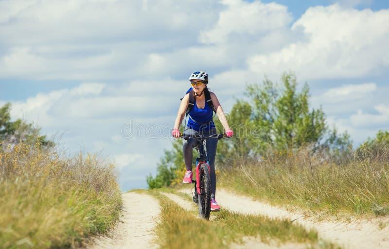 Una mujer joven - un atleta monta en una bici de montaña fuera de la ciudad en el camino en el bosque fotos de archivo libres de regalías