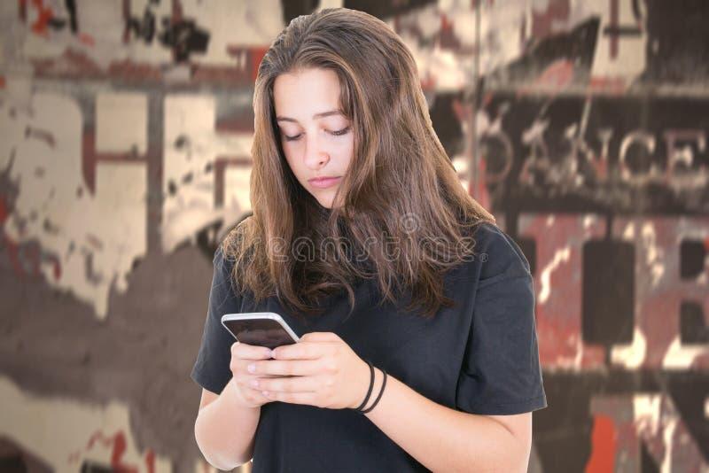 Una mujer joven usando un smartphone en la muchacha de la ciudad que manda un SMS en un teléfono elegante imágenes de archivo libres de regalías