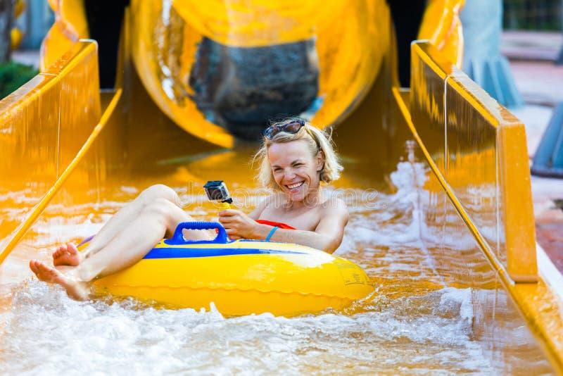 Una mujer joven vino abajo del tobogán acuático en un círculo de goma con una cámara en su mano foto de archivo