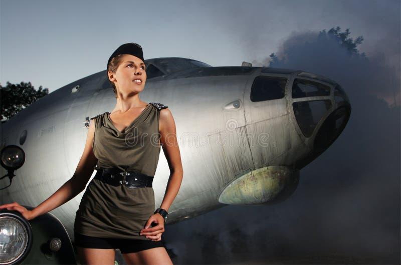 Una mujer joven y atractiva que presenta cerca de un aeroplano imagen de archivo libre de regalías