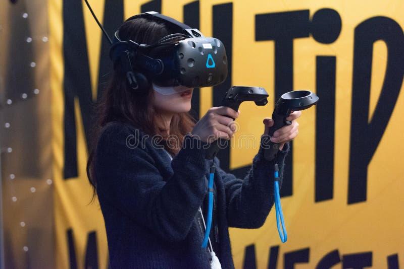 Una mujer juega a un videojuego usando los vidrios de la realidad virtual fotos de archivo libres de regalías