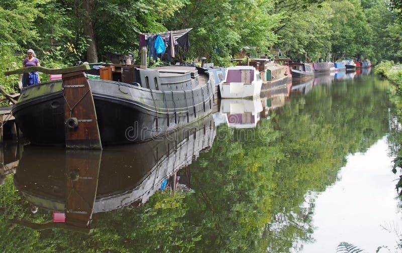 Una mujer junto a barcas y barcazas amarradas en el canal rochdale en el puente de Hebden rodeado de verdes árboles de verano fotos de archivo