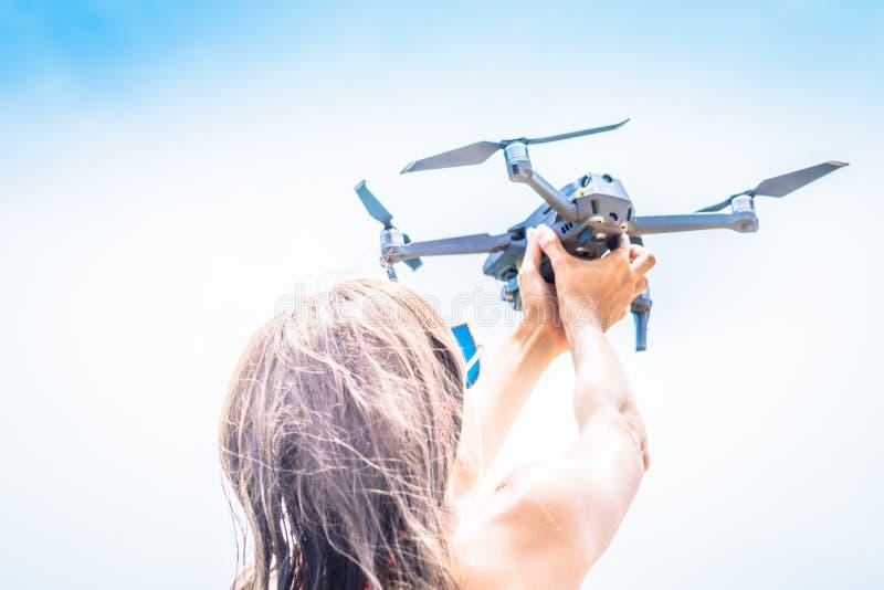 Una mujer lanza un abejón para el vuelo, con el cual usted puede tomar las fotos y la película video imagen de archivo