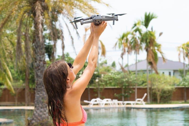 Una mujer lanza un abejón para el vuelo, con el cual usted puede tomar las fotos y la película video fotografía de archivo libre de regalías