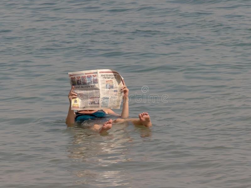 Una mujer lee un periódico mientras que flota en el mar muerto imagen de archivo
