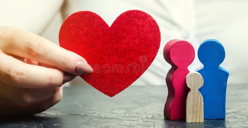 Una mujer lleva a cabo en sus manos un coraz?n rojo cerca de una familia miniatura Concepto de vida y de seguro m?dico Servicios  imágenes de archivo libres de regalías