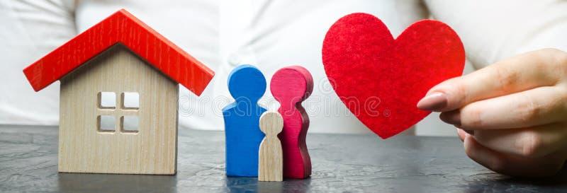 Una mujer lleva a cabo en sus manos un coraz?n rojo cerca de una familia y de un hogar miniatura El concepto de seguro de propied fotografía de archivo