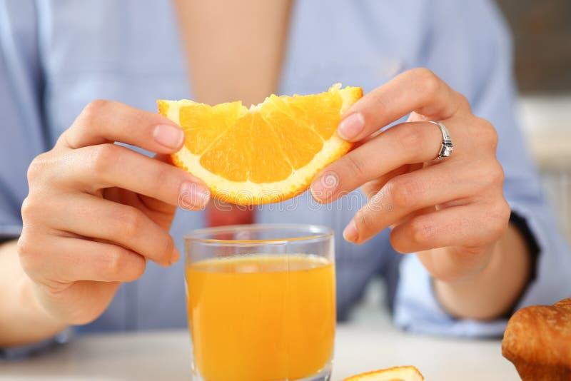 Una mujer lleva a cabo una rebanada de naranja cortada fotografía de archivo