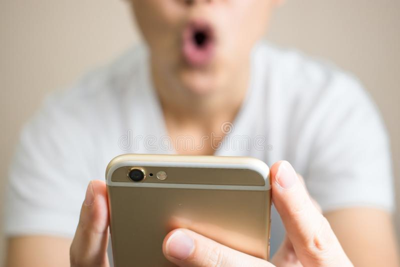 Una mujer lleva las camisetas blancas muy chocadas Después de recibir un mensaje del teléfono fotografía de archivo libre de regalías