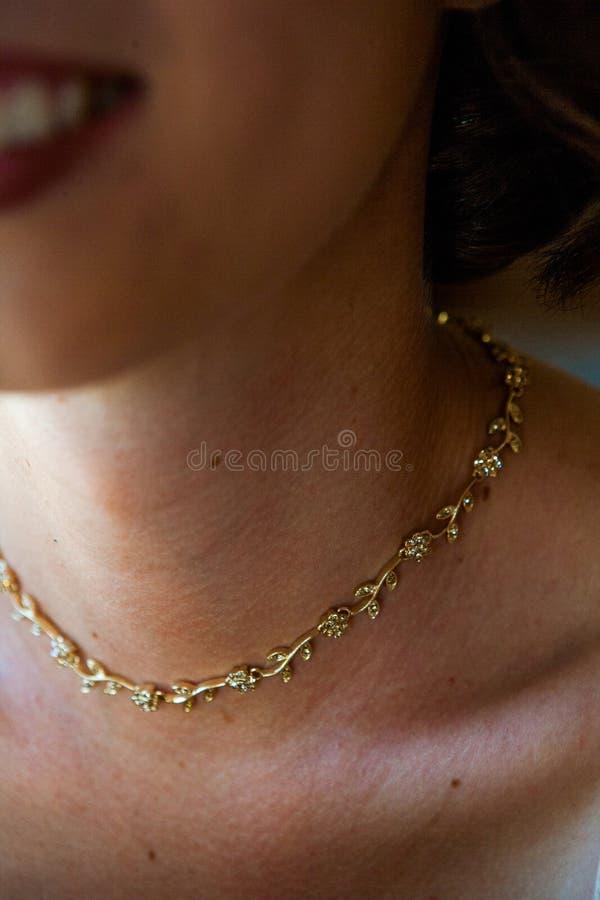 Una mujer lleva un collar de oro del vintage alrededor de su cuello fotos de archivo