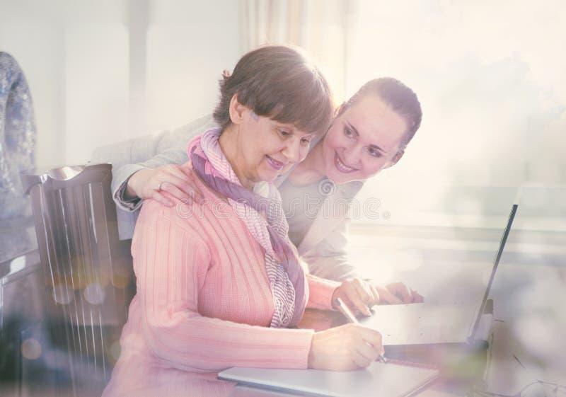 Una mujer más joven que ayuda a una persona mayor que usa el ordenador portátil fotos de archivo
