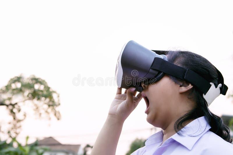 Una mujer más joven que lleva los vidrios de la realidad virtual con la situación asombrosamente de la cara al aire libre imagenes de archivo