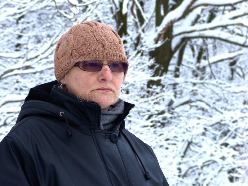 Una mujer madura contra la perspectiva de árboles nevosos imágenes de archivo libres de regalías