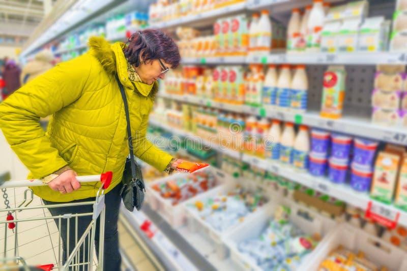 Una mujer madura hermosa elige los productos lácteos en el supermercado foto de archivo libre de regalías