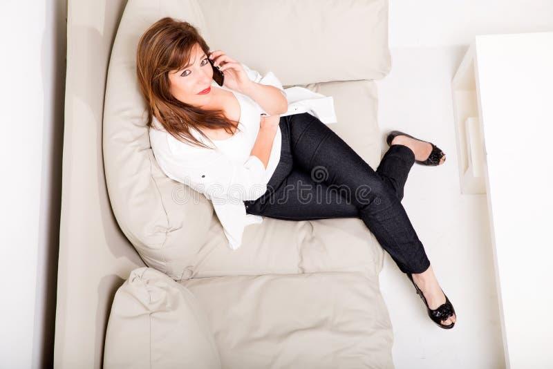 Una mujer madura que habla en su teléfono celular en el sofá imagen de archivo libre de regalías